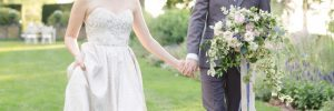 Bride and groom in the garden holding hands