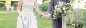 Bride and groom in the garden holding hands
