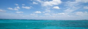 Blue Caribbean waters under lightly clouded sky