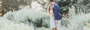 Recently engaged couple walk in formal gardens