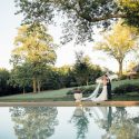 Bride and groom by pool at sunset