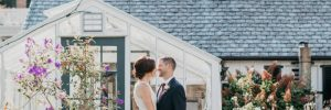Bride and groom in front of greenhouse at Drumore Estate