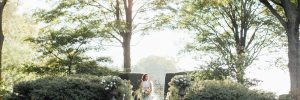 Bride along stone in garden holding large bridal bouquet