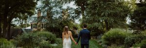 Bride and groom walking towards the mansion
