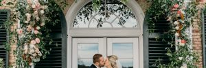 Bride and groom kissing under arch at Drumore Estate