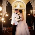 Bride and groom kissing with wedding guests lighting sparklers