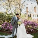 Groom kissing bride along with purple flowers at Drumore Estate garden