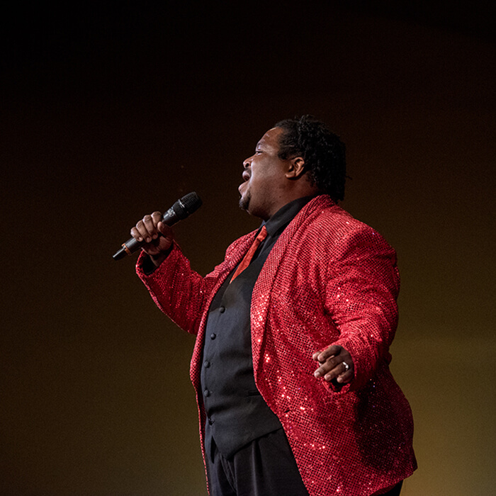 Cabaret performer wearing red sequin blazer
