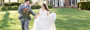 Bride and groom running through the front lawn of mansion