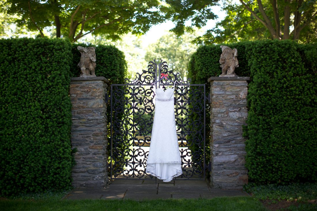 wedding-gown-hanging-on-cast-iron-gate-1100×733